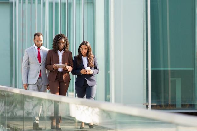 Erfolgreiches geschäftsteam, das städtische glaswand im freien entlanggeht