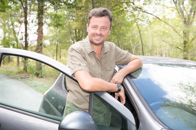 Erfolgreiches glückliches stehendes nahes auto des jungen mannes