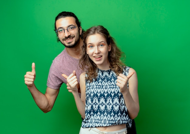 Erfolgreiches junges paar mann und frau betrachten kamera lächelnd fröhlich daumen hoch über grünem hintergrund zeigend