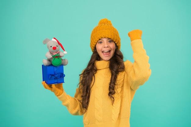 Erfolgreiches rattenjahr. mit geschenk besänftigen. einkaufstipps. glückliches mädchen hält mausspielzeug und verpackte geschenkbox. kinder strickpullover und mütze spielen plüschtier. für kinder einkaufen. frohes jahr 2020. geschenk für viel glück.