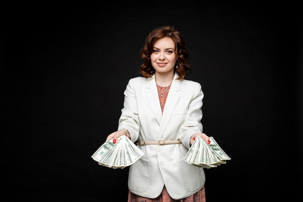 Erfolgreiches stilvolles brünettes modell mit geld in händen.