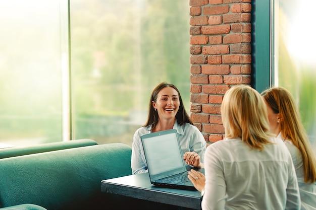 Erfolgreiches team. drei selbstbewusste geschäftsfrau trägt weiße hemden, die einander ansehen und lächeln, während sie am schreibtisch im büro mit einem laptop auf dem schreibtisch sitzen.