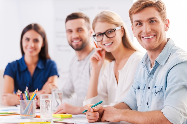 Erfolgreiches team. gruppe selbstbewusster geschäftsleute in smarter freizeitkleidung, die zusammenarbeiten und lächeln