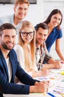 Erfolgreiches und kreatives team. gruppe selbstbewusster geschäftsleute in smarter freizeitkleidung, die zusammenarbeiten und lächeln