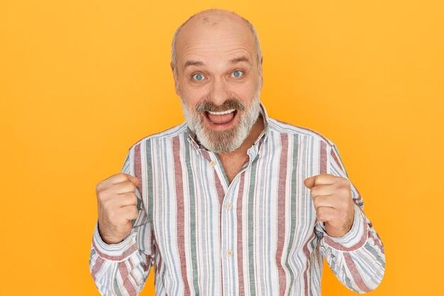 Erfolgs-, feier-, aufregungs- und siegeskonzept. fröhlicher älterer mann mit dickem bart, der die fäuste ballt und schreit ja