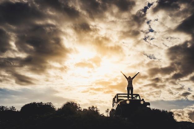 Erfolgs- und einsames reisender-konzept mit einem mädchen in silhouette, das auf seinem auto steht und die arme zum dramatischen himmel eines goldenen sonnenuntergangs öffnet