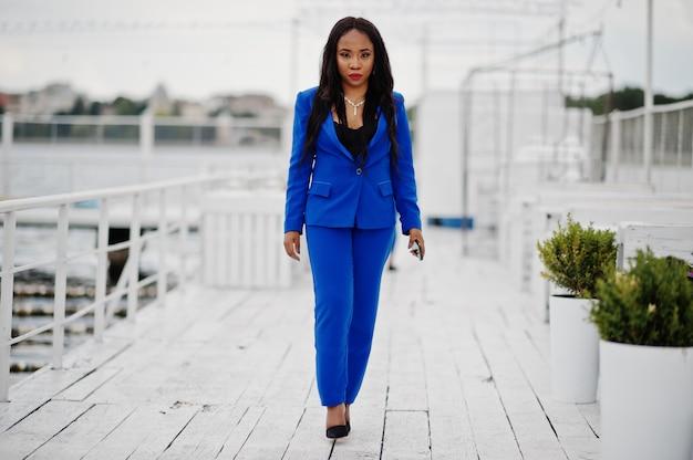 Erfolgsafroamerikaner-geschäftsfrau an der blauen klage mit handy.