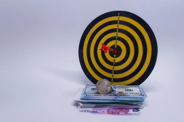 Erfolgskonzept und zielerreichung. runde dartscheibe mit einem bündel dollar, euro und einer bitcoin-münze.