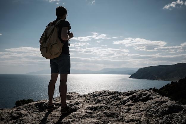 Erfolgskonzept. wanderer mit rucksack, der auf einem berg mit erhobenen händen steht und ansicht genießt
