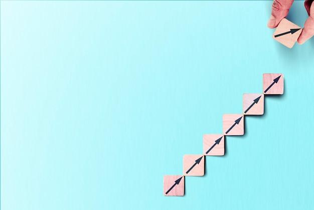 Erfolgsprozess für das wachstum von geschäftskonzepten. holzblockstapelung als stufentreppe mit pfeil nach oben.