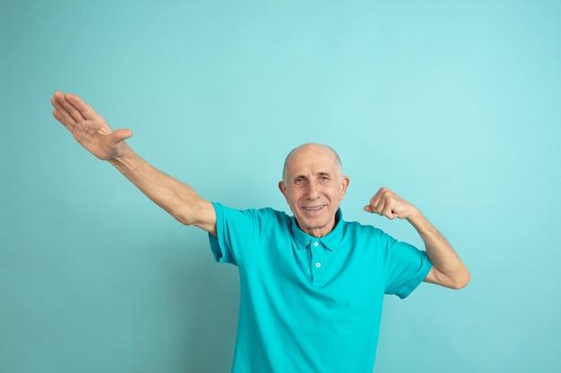 Erfolgssiegergeste. porträt des kaukasischen älteren mannes auf blauem studiohintergrund. schönes männliches emotionales modell. konzept der menschlichen emotionen, gesichtsausdruck, verkauf, wohlbefinden, anzeige. copyspace.