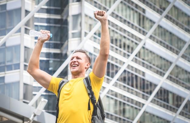 Erfolgssport-mannreisender in der modernen stadt mit aufregung