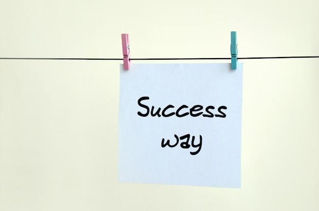Erfolgsweg hinweis ist auf einem weißen aufkleber geschrieben, der hängt