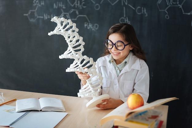 Erforschung der genetischen code-mutation. erfahrener glücklicher kleiner schüler, der im labor sitzt und mikrobiologieunterricht genießt, während er chromosomenmodell studiert und erforscht