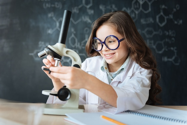Erforschung der molekularen welt. lächelnder schlauer fähiger forscher, der im labor sitzt und chemieunterricht genießt, während er am mikrobiologieexperiment teilnimmt und das mikroskop benutzt