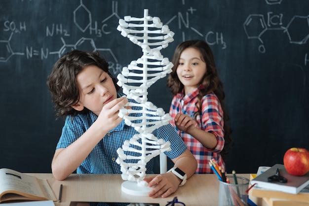 Erforschung der veränderung des genoms. emotioanal beinhaltete begeisterte kinder, die in der schule saßen und den chemieunterricht genossen, während sie an die tafel schrieben und das genetische codemodell verwendeten Premium Fotos