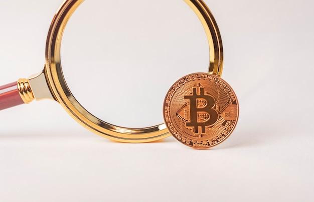 Erforschung und untersuchung von btc- oder bitcoin-münzen mit vergrößerungslinse auf weiß.