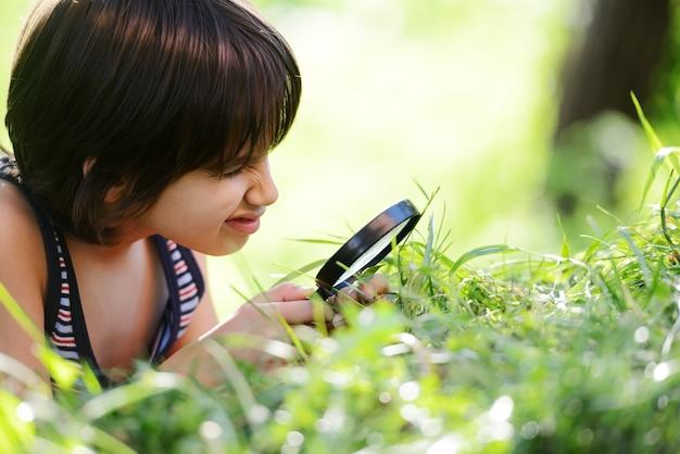 Erforschungsnatur des glücklichen kindes mit lupe