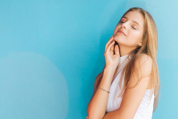 Erfreuliche hübsche blonde junge frau gegen blauen hintergrund