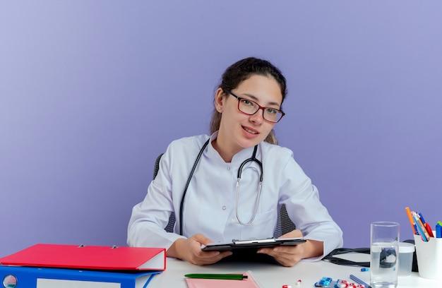 Erfreuliche junge ärztin, die medizinische robe und stethoskop trägt, sitzt am schreibtisch mit medizinischen werkzeugen, die halteklemmbrett isoliert suchen