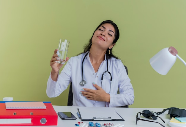 Erfreuliche junge ärztin, die medizinische robe und stethoskop trägt, sitzt am schreibtisch mit medizinischen werkzeugen, die hand auf brust halten glas des wassers mit geschlossenen augen isoliert