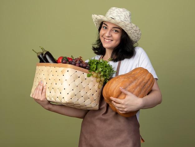 Erfreuliche junge brünette gärtnerin in uniform, die gartenhut trägt, hält gemüsekorb und kürbis lokalisiert auf olivgrüner wand