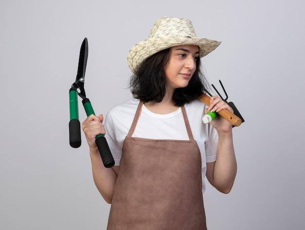 Erfreuliche junge brünette gärtnerin in uniform mit gartenhut hält gartengeräte, die die seite lokalisiert auf weißer wand betrachten