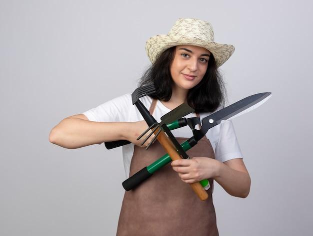 Erfreuliche junge brünette gärtnerin in uniform mit gartenhut hält gartengeräte isoliert auf weißer wand mit kopierraum