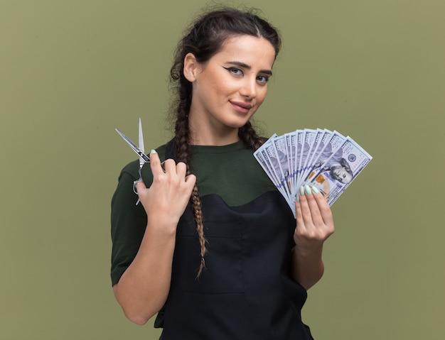Erfreuliche junge friseurin in uniform, die bargeld mit schere auf olivgrüner wand isoliert hält