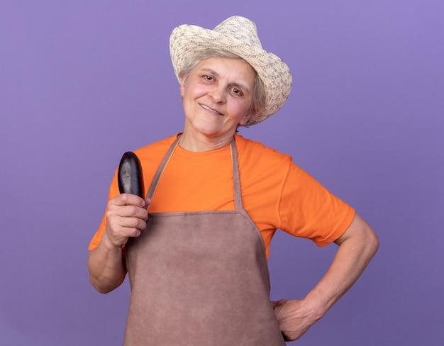 Erfreulicher älterer weiblicher gärtner, der gartenhut trägt, der aubergine auf purpur hält