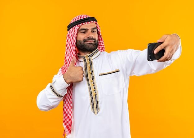 Erfreulicher arabischer geschäftsmann in traditioneller kleidung, der selfie unter verwendung seines smartphones nimmt, das zuversichtlich steht, über orange wand zu stehen