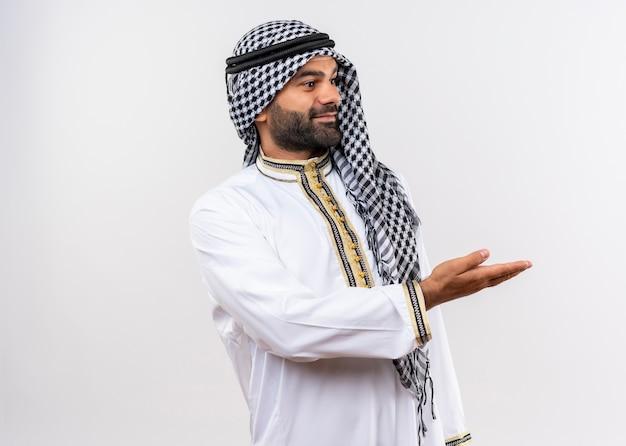 Erfreulicher arabischer mann in traditioneller kleidung, die beiseite schaut und kopienraum mit arm der hand darstellt, der über weißer wand steht