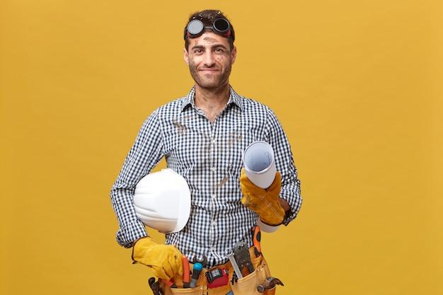 Erfreulicher arbeiter eines schmutzigen mannes, der eine schutzbrille auf dem kopf hat und gerolltes papier mit helm hält, der über gelber wand isoliert wird. professioneller hübscher mann mit gürtel der werkzeuge, die zur arbeit gehen