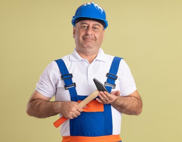 Erfreulicher erwachsener baumeister in uniform hält hammer isoliert auf olivgrüner wand