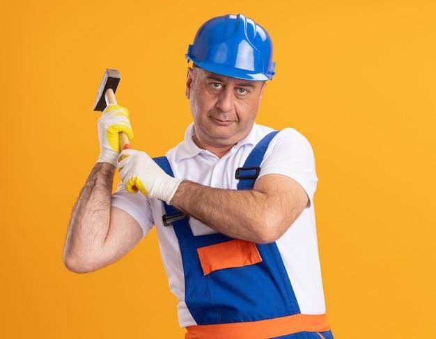 Erfreulicher erwachsener baumeistermann in der uniform, die schutzhandschuhe trägt, die hammer lokalisiert auf orange wand halten