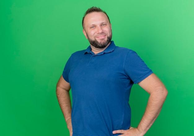 Erfreulicher erwachsener slawischer mann, der hände auf taille lokalisiert auf grüner wand mit kopienraum setzt