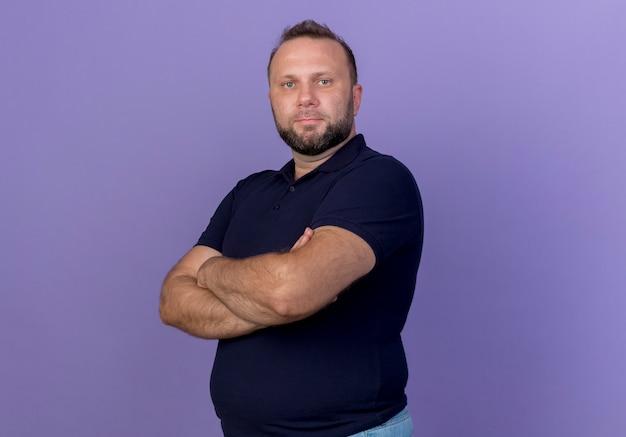 Erfreulicher erwachsener slawischer mann, der mit geschlossener haltung in der profilansicht isoliert steht