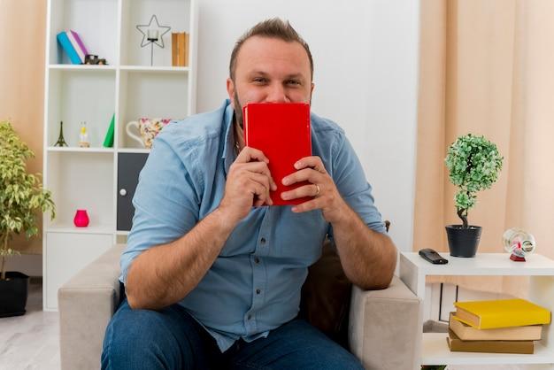 Erfreulicher erwachsener slawischer mann sitzt auf sessel und hält buch vor mund im wohnzimmer