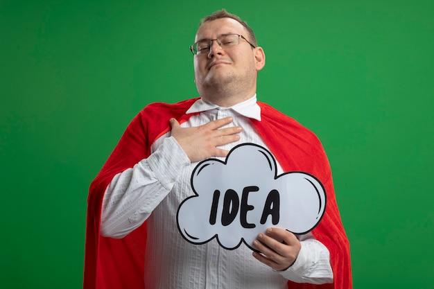 Erfreulicher erwachsener slawischer superheldenmann im roten umhang, der die brille hält, die ideenblase hält, die hand auf brust setzt, kamera betrachtet auf grünem hintergrund