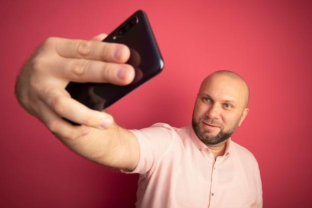Erfreulicher glatzkopf mittleren alters, der rosa t-shirt trägt, nehmen ein selfie, das auf rosa isoliert wird
