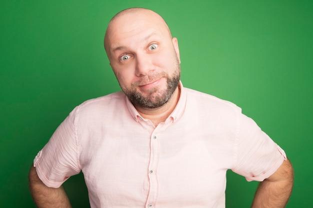 Erfreulicher glatzkopf mittleren alters, der rosa t-shirt trägt