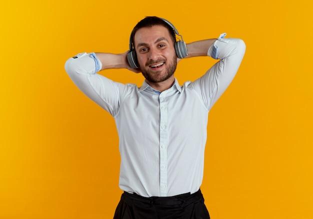 Erfreulicher gutaussehender mann auf kopfhörern hält kopf hinter mit händen, die auf orange wand isoliert sind