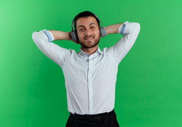 Erfreulicher gutaussehender mann auf kopfhörern legt hände hinter kopf isoliert auf grüne wand