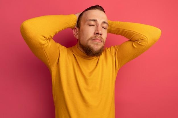 Erfreulicher hübscher blonder mann steht mit geschlossenen augen und legt hände auf kopf auf rosa