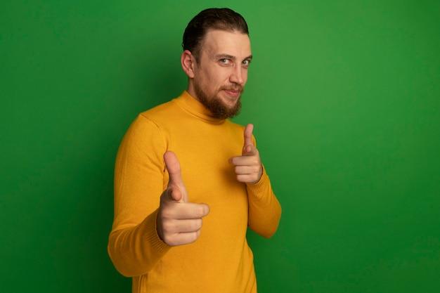 Erfreulicher hübscher blonder mann zeigt mit zwei händen auf grün auf kamera