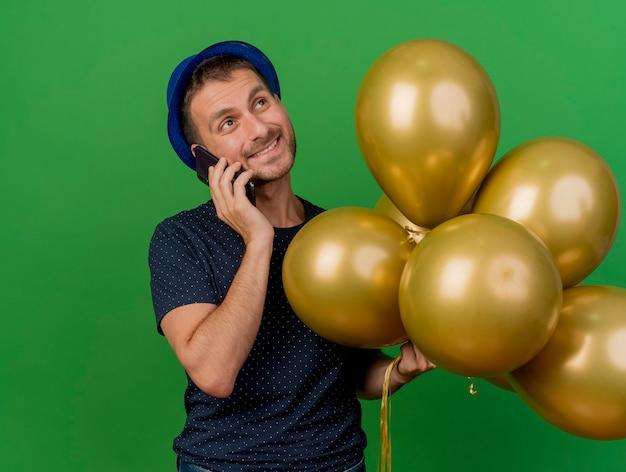 Erfreulicher hübscher kaukasischer mann, der blauen parteihut trägt, hält heliumballons, die am telefon sprechen, das seite lokalisiert auf grünem hintergrund mit kopienraum betrachtet