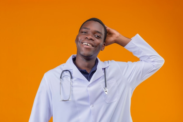 Erfreulicher junger afroamerikanerarzt, der weißen kittel mit dem fröhlich lächelnden stethoskop trägt