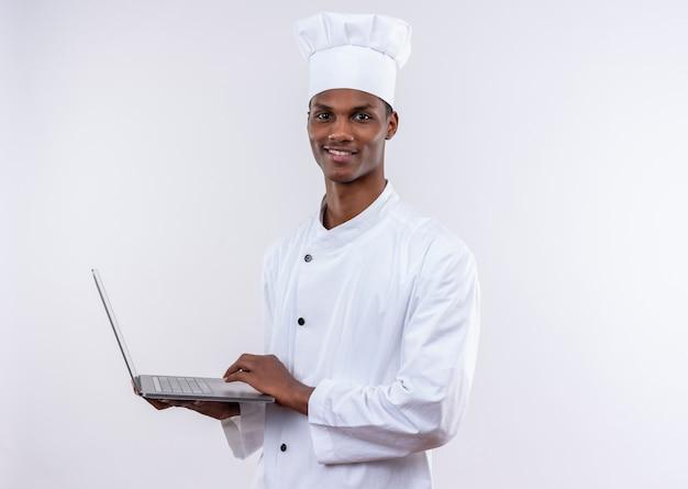 Erfreulicher junger afroamerikanischer koch in der kochuniform hält laptop und betrachtet kamera auf lokalisiertem weißem hintergrund mit kopienraum