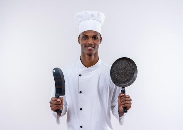 Erfreulicher junger afroamerikanischer koch in der kochuniform hält messer und bratpfanne auf lokalisiertem weißem hintergrund mit kopienraum