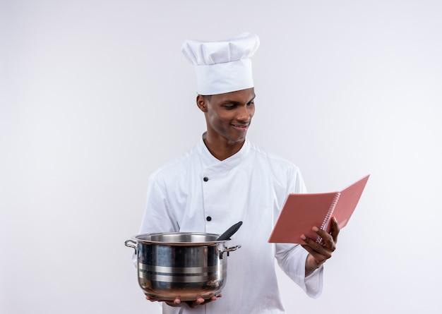Erfreulicher junger afroamerikanischer koch in der kochuniform hält topf und betrachtet notizbuch auf lokalisiertem weißem hintergrund mit kopienraum
